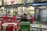 A Grab Holdings Inc. driver waits for an order outside a restaurant in Jalan Alor area in Kuala Lumpur, Malaysia, on Monday, Sept. 28, 2020. On Sunday, Malaysia saw the highest daily surge in coronavirus cases since Sept. 11, including the emergence of a new cluster in Kuala Lumpur. Photographer Ian Teh/Bloomberg