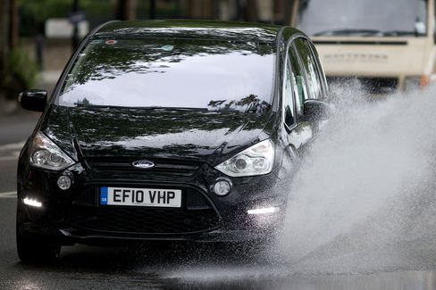 A car drives through a large puddle left after heavy rain in central London, England, on July 8, 2012.
