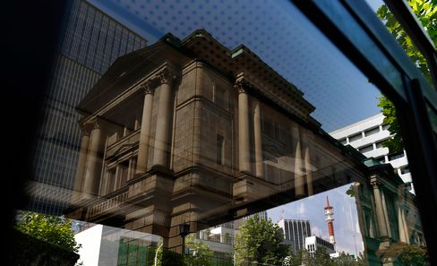 The Bank of Japan headquarters is reflected on a telephone booth window in Tokyo, Japan.