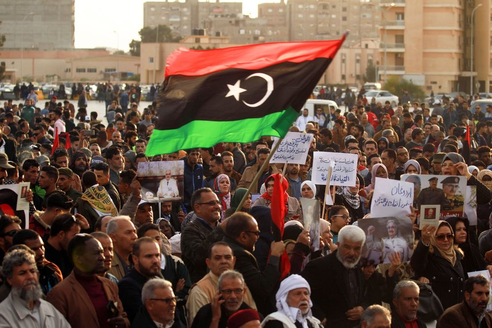 Supporters of Khalika Haftar wave a national during a demonstration in Libya.