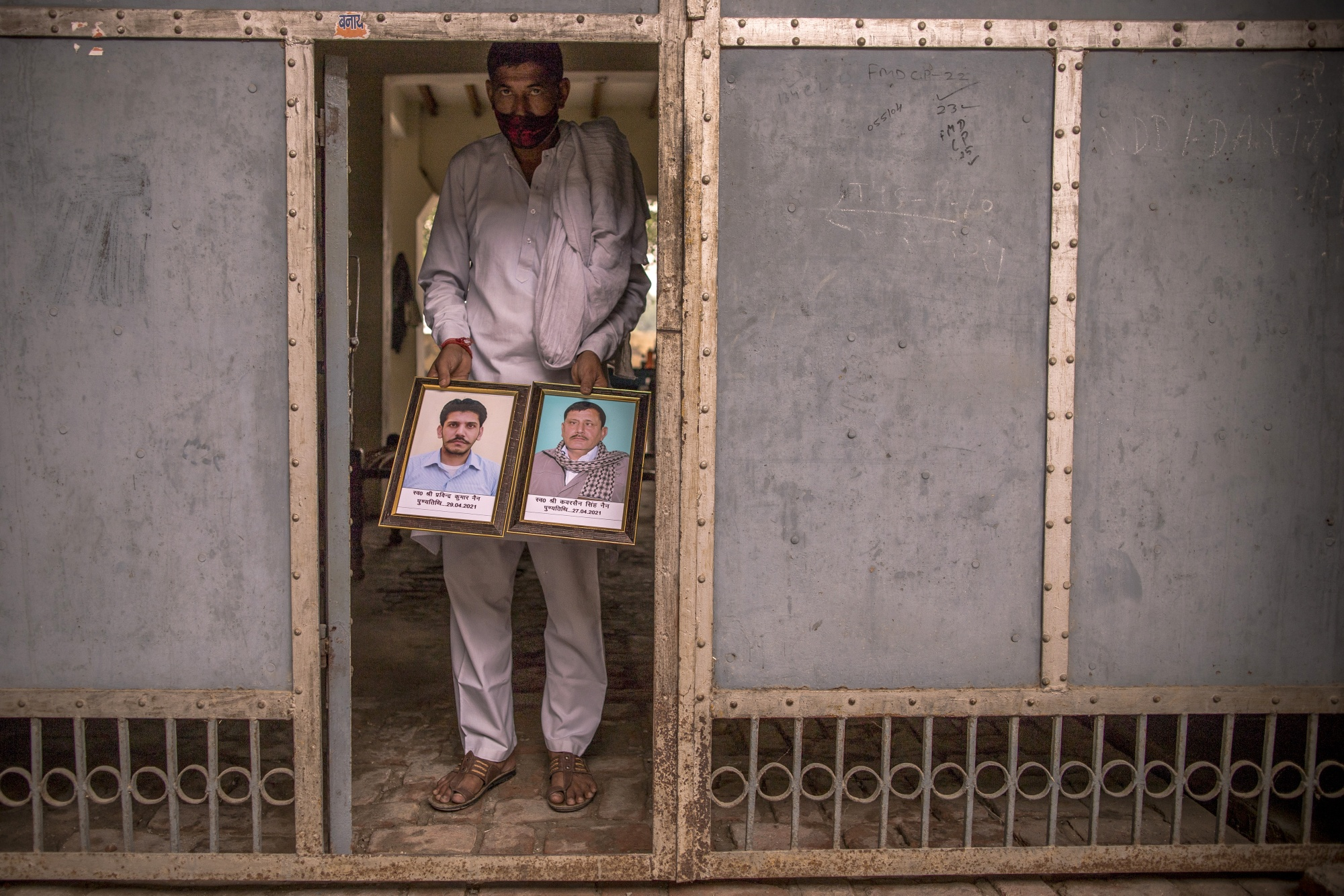 Village Pradhan / Head brings out the portrait of Covid fatalities Kuwarsen Singh (R) and his son Pravinder Kumar. Kuwarsen singh was sent to an election duty where he was infected with the Covid virus. Picture taken at his house in the village Bassi, in Baghpath, Uttar Pradesh, India