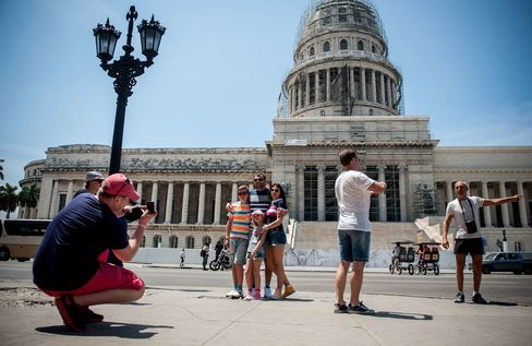 U.S. tourists pose in front of the Capitol in Havana on April 6, 2015.