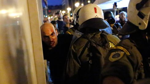 Riot police detains an anti-austerity protester during clashes in Athens on July 15, 2015.