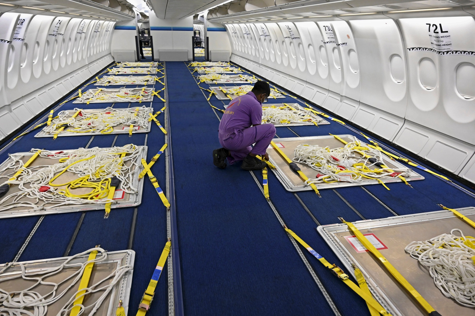 A Sri Lankan Airlines worker gives final touches to an Airbus A330 passenger aircraft, converted into a cargo carrier, in June 2020.
