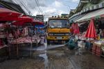 A sanitation worker uses a high-pressure water hose to wash down a market in Bangkok, on March 25.