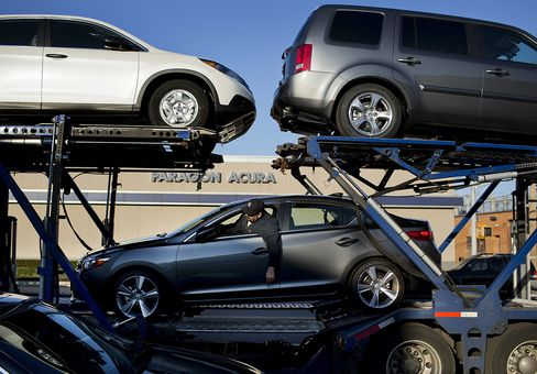 Workers unload a truck carrying new Honda automobiles at a dealership in Queens, New York.
