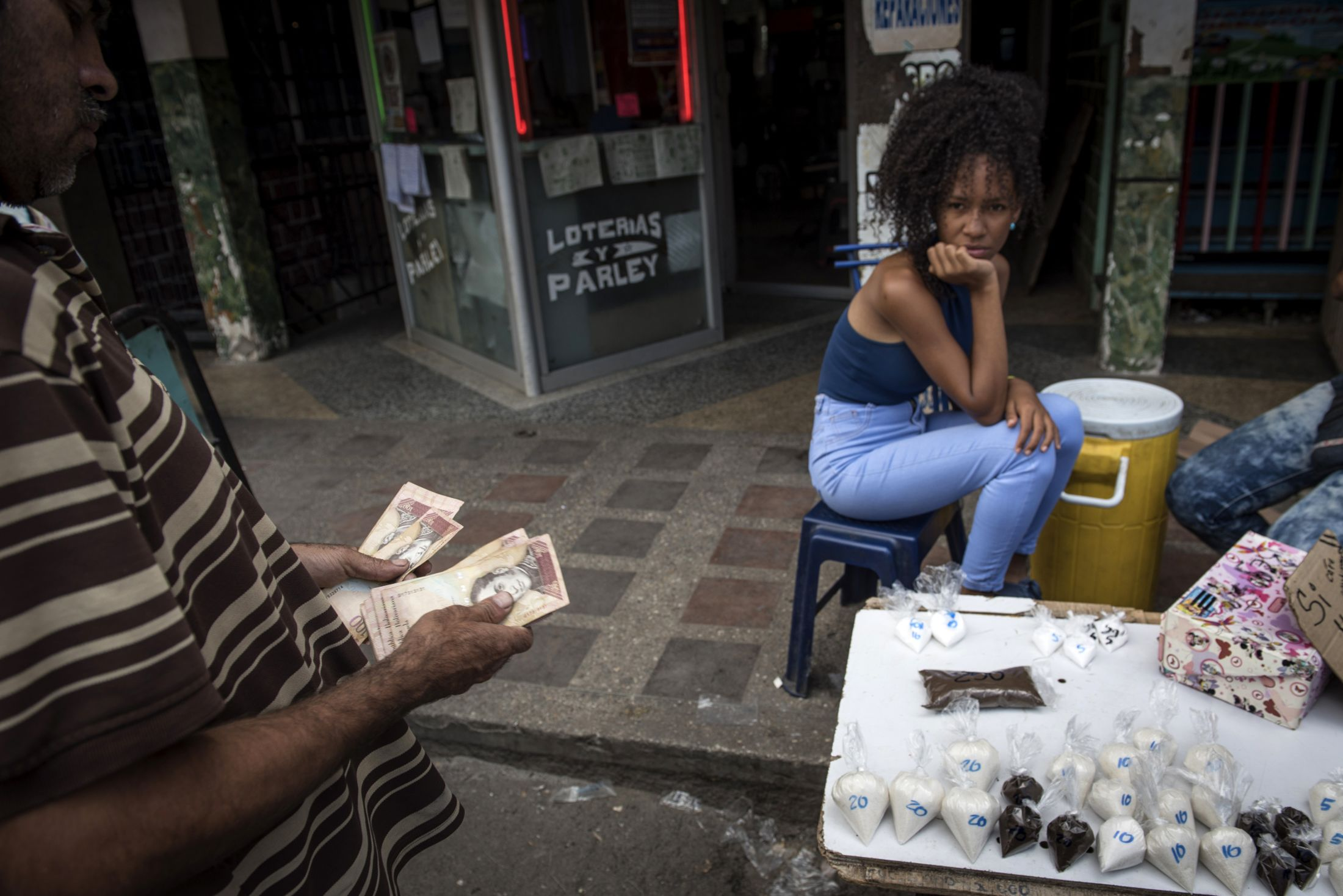 A customer counts Bolivar banknotes before purchasing coffee and sugar in the Petare slum of Caracas.