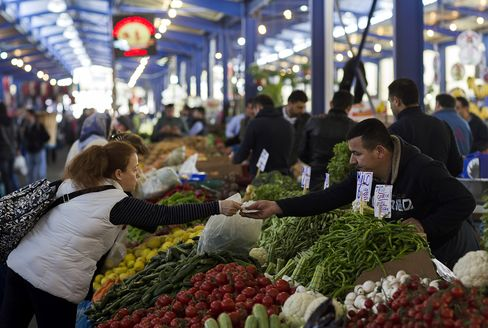 A Trader Accepts Lira for Vegetables at a Market in Istanbul