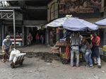 Members of the Bolivarian National Guard stand guard as shoppers browse goods at the Municipal Market of Quinta Crespo in Caracas, Venezuela.
