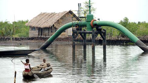 Children sail past an oil pipeline head