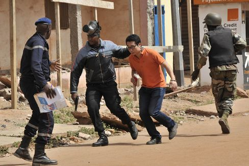 Malian security forces evacuate a man from the Radisson Blu hotel in Mali