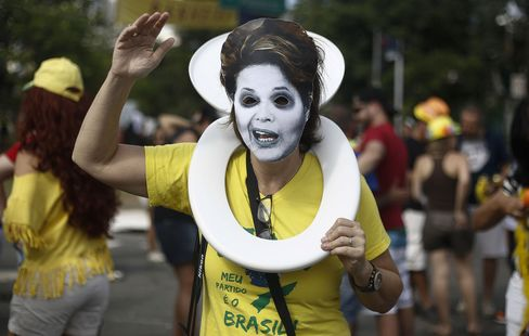 A reveler wears a mask depicting President Dilma Rousseff during a bloco.