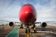 An employee carries out checks on a Boeing Co. 787 Dreamliner passenger aircraft operated by Norwegian Air Shuttle AS, at Gatwick Airport outside London.