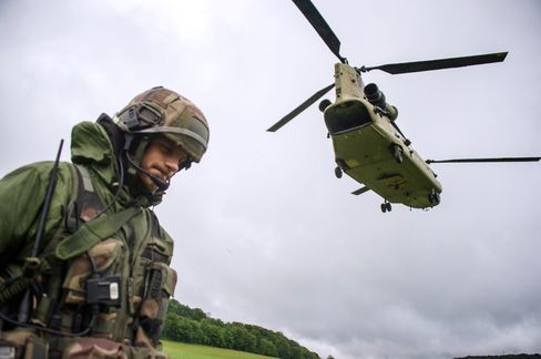 Chinook helicopter passes over a French soldier during a French-US 'Royal Blackhawk' military exercise with French, US, Dutch, British and Belgian troops, on May 20, 2015, in Baume-Les-Dames, eastern France.