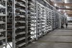 A technician inspects bitcoin mining machines at a mining facility operated by Bitmain Technologies Ltd. in Ordos, Inner Mongolia, China.