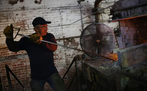 A worker stokes the fire after throwing buckets of scrap glass into the flames during marble production at a manufacturing facility in Paden City, W.Va.