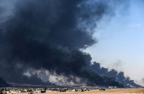 Smoke rises from burning oil wells south of Mosul on Oct. 18.