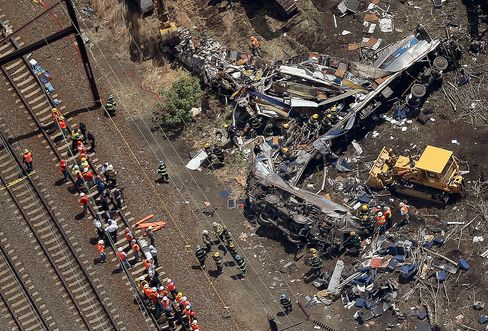 Investigators and first responders work near the wreckage of the crash on May 13, 2015 in north Philadelphia, Pennsylvania.
