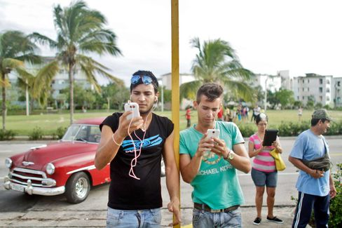 Dozens of Cubans stand in front of the Hotel Pernik and use phones, tablets, and laptops to connect to the Wi-Fi signal coming from the hotel on Sept. 21, 2015, in Holguin, Cuba.