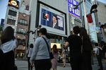 People wait for a traffic signal to change as a screen displays a live broadcast of Prime Minister Shinzo Abe speaking at a news conference in Tokyo, Japan, on Friday.