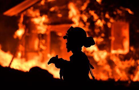住宅火災の状況監視に当たる地元消防隊員(10月9日)