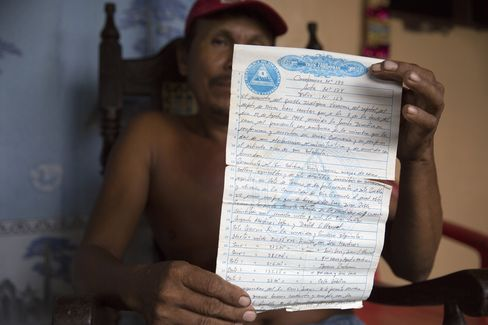 A resident holds his land contract near the Hacienda Miramar, where work has started on the canal in Rio Grande, Nicaragua.