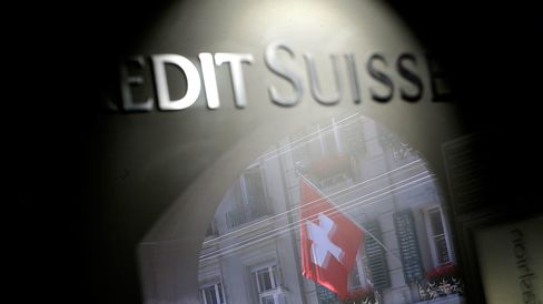 The Swiss national flag is seen reflected in the window of a Credit Suisse Group AG bank branch in Bern, Switzerland.