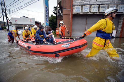 Rescue workers transport evacuees through floodwaters at Oyama in Tochigi prefecture, north of Tokyo on Sept. 10, 2015.