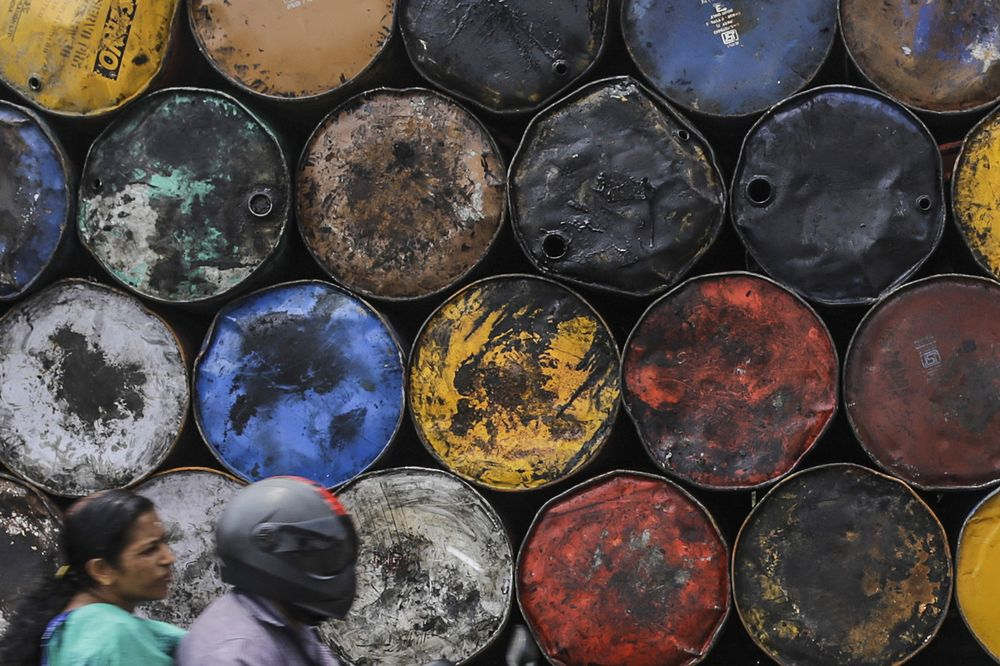 A motorcyclist drives past stacked oil drums in Cochin, India.