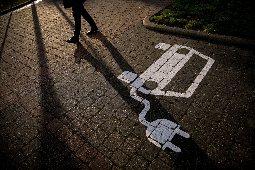 A pedestrian passes an empty electric vehicle charge space in a parking lot in Gruenheide, Germany.