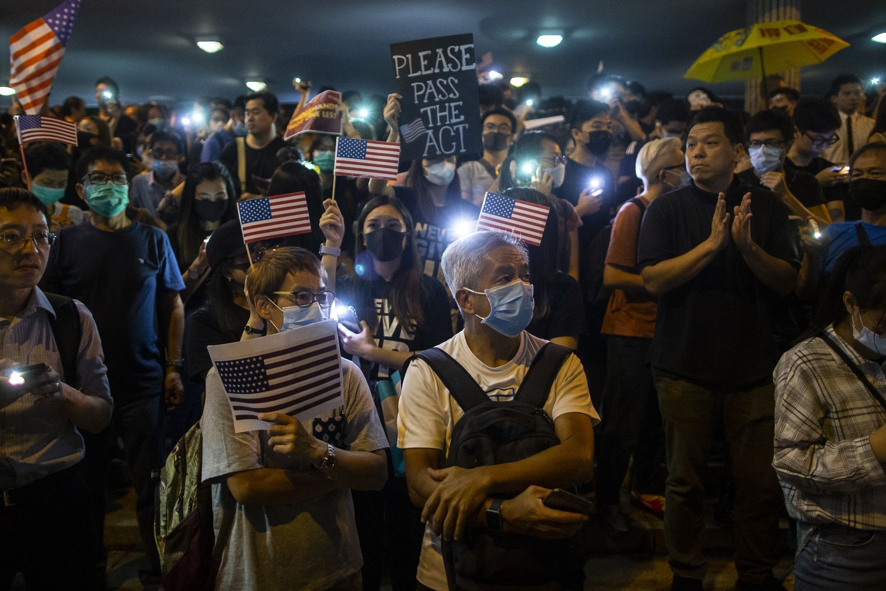Demonstrators hold placards and the American flag during a rally in support of the Hong Kong Human Rights and Democracy Act in Hong Kong.