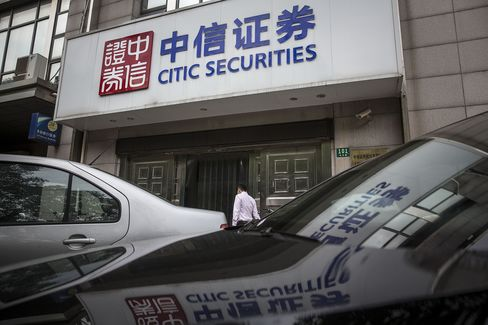 A pedestrian walks past a Citic Securities branch in Shanghai, China.