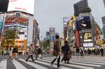 Pedestrians walk across a road in the Shibuya district of Tokyo, Japan.