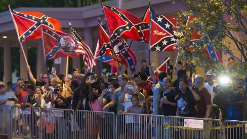People wave Confederate flags as President Barack Obama arrives at his hotel in Oklahoma City on July 15, 2015.