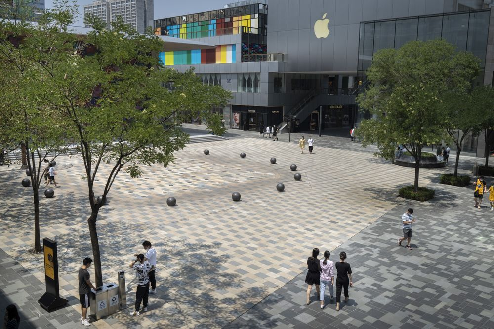 Pedestrians walk through a plaza in front of an Apple Inc. store in the Sanlitun area in Beijing on July 15.