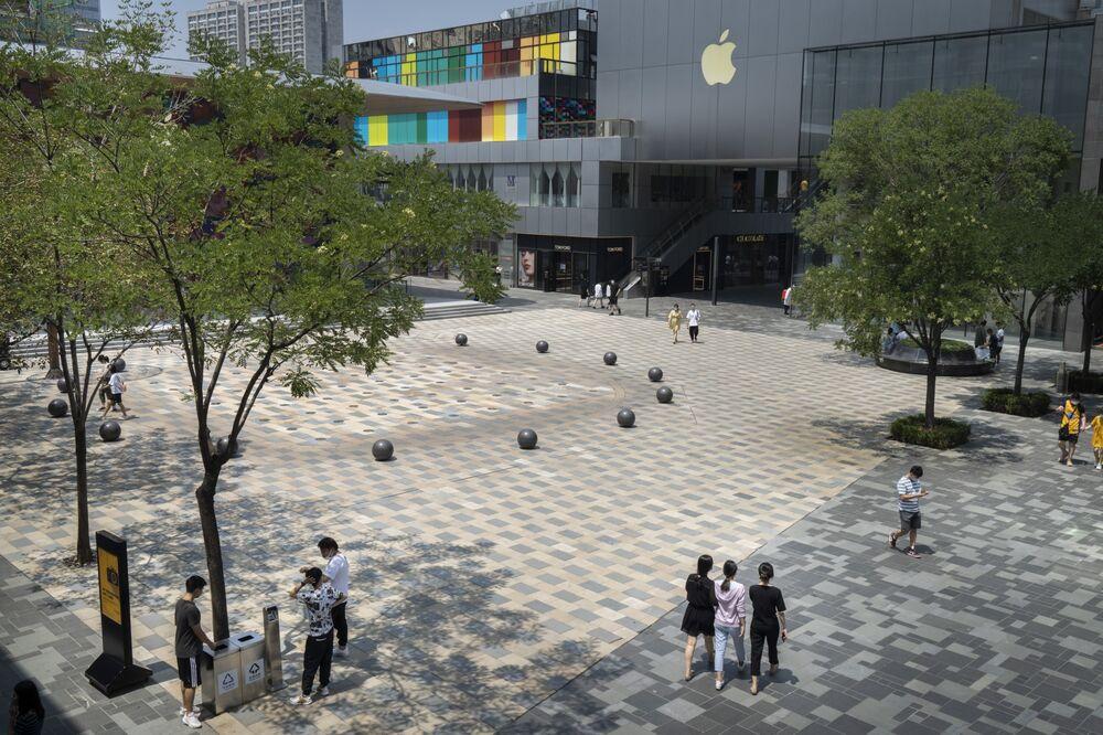 Người đi bộ đi qua một quảng trường trước một cửa hàng Apple Inc. ở khu vực Sanlitun ở Bắc Kinh vào ngày 15 tháng 7. Nhiếp ảnh gia: Giulia Marchi / Bloomberg