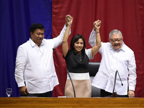 Philippine Senate president Frank Drilon and House speaker Feliciano Belmonte raise the hands of vice president-elect Leni Robredo during her proclamation as vice president at the Session Hall of the House of Representatives in Manila on Monday.