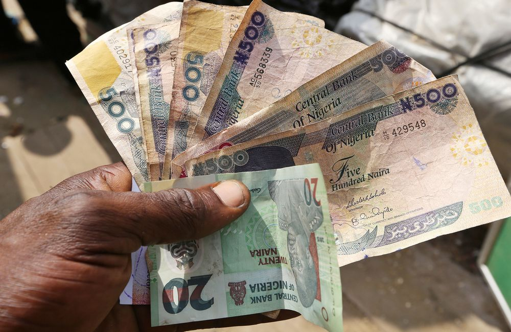 A Trader Holds 20 And 500 Denomination Naira Banknotes At The Swali Market In Yenagoa