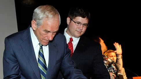 Then-Representative Ron Paul signs a copy of the U.S. Constitution for a supporter as his campaign manager, Jesse Benton, looks on in Las Vegas on May 17, 2011.