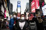 Pedestrians wearing protective masks walk through the Times Square neighborhood of New York, U.S., on Thursday, March 12, 2020.