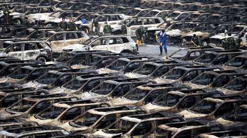 Rescue workers clear away debris next to rows of burnt cars in a parking lot near the site of the massive blasts in Tianjin, China.