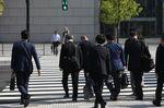 Morning commuters walk across a road in Tokyo.