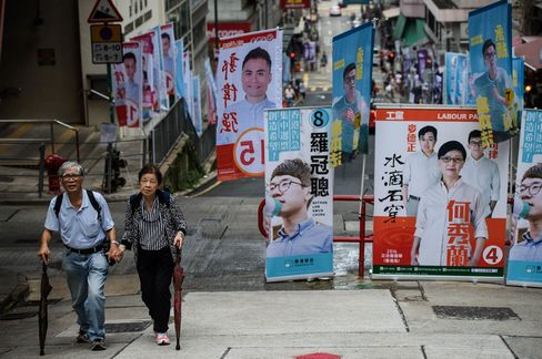 A couple walk past campaign banners during the Legislative Council election in Hong Kong on Sept. 4.