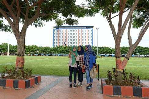 Teenagers take a 'selfie' photograph beside a clean, well-tended Bantaeng park.