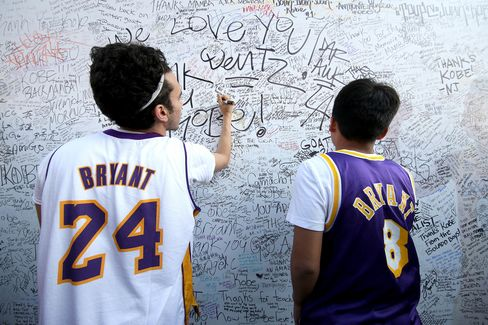Fans sign an autograph board outside the Staples Center.