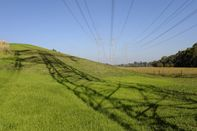 The shadow of a power transmission pylon is cast over grassy hill as power lines hang overhead in Melbourne, Australia.