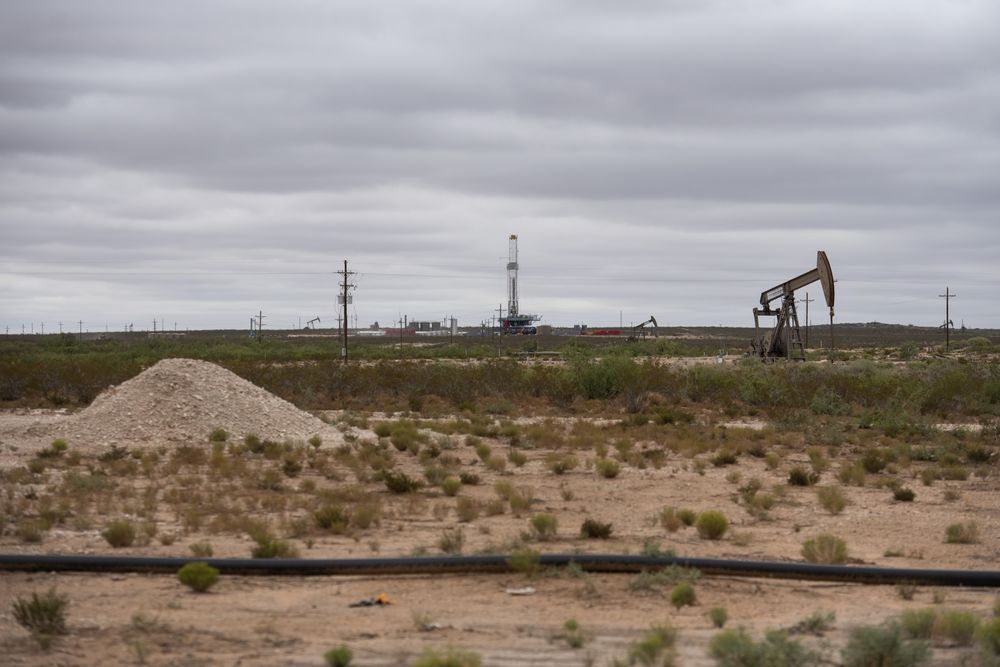 A horizontal drilling rig and a pump jack in Lea County, New Mexico.