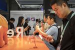 Attendees look at smartphones displayed at the Oppo booth at the MWC Shanghai exhibition in Shanghai, China, on Thursday, June 27, 2019.