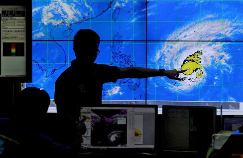 Meteorologists from the Philippine Atmospheric, Geophysical and Astronomical Services Administration monitor and plot the direction of super typhoon Maysak at PAGASA headquarters in Manila on April 1, 2015.