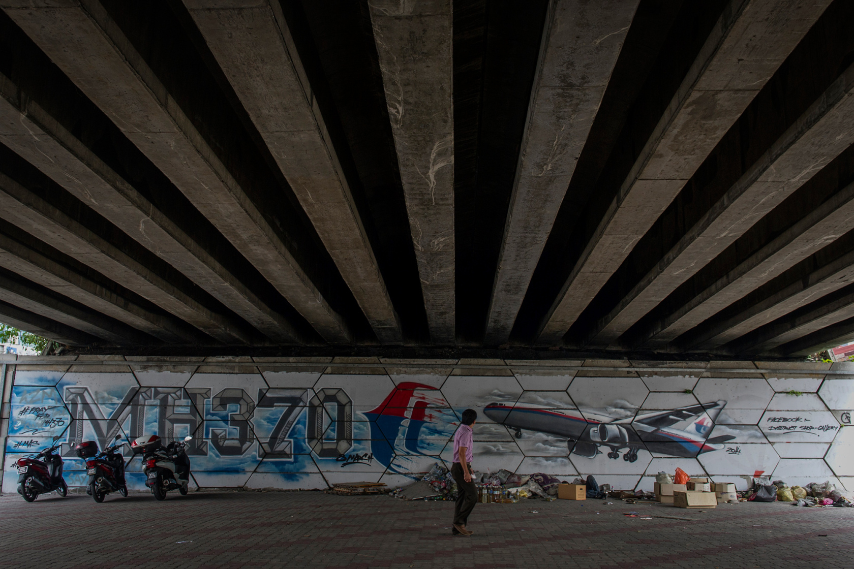An unidentified man walks past MH370 related street art under a flyover in Kuala Lumpur, Malaysia.